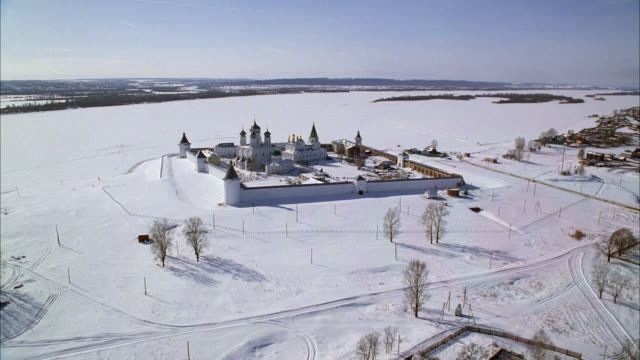 AERIAL OF MAKARIEV MONASTERY NEAR NIZHNY NOVGOROD ON THE VOLGA RIVER. COULD BE FORTRESS, CASTLE, CONVENT, RUSSIAN ORTHODOX CHURCH OR CATHEDRAL. SNOW. WALLS WITH GUARD TOWERS, TURRETS. ONION DOMES. RUSSIAN COUNTRYSIDE OR RURAL AREA.