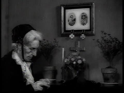 vídeos de stock, filmes e b-roll de 1938 woman knitting beneath photographs of soldiers german war medals dangling beneath the frames - só uma mulher idosa