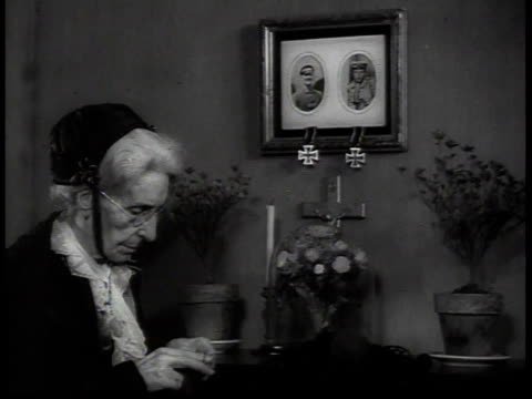 woman knitting beneath photographs of soldiers, german war medals dangling beneath the frames - war stock-videos und b-roll-filmmaterial