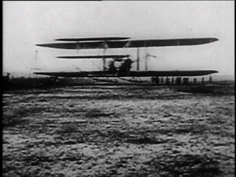 1900s MONTAGE Early creaky biplane taking off for flight / Dayton Ohio United States