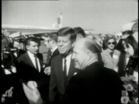 november 1963 montage president john f kennedy and his wife jaqueline kennedy onassis being welcomed at dallas airport / texas united states - attentat auf john f. kennedy stock-videos und b-roll-filmmaterial