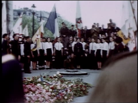 vidéos et rushes de crowd in front of eternal flame at the tomb of the unknown soldier beneath the arc de triomphe / paris france - arc de triomphe paris