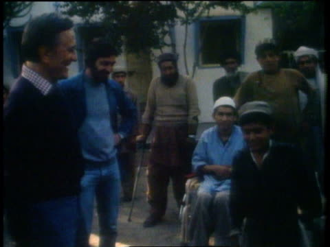 kirk douglas shaking hands with boy with no legs / peshawar, pakistan - peshawar stock videos & royalty-free footage