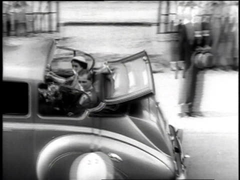 vidéos et rushes de queen elizabeth ii drives away in back of car and then using a shovel plants a cottonwood tree to initiate island reforestation program while on her... - 1953
