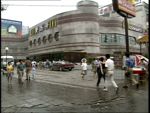 December 7 1993 MONTAGE Patrons and passersby walking past McDonald's golden arches / China