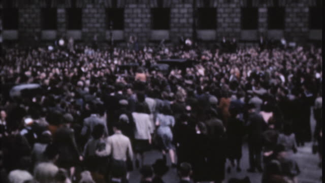 pan large crowd celebrating and gathering at buckingham palace on ve day / london england united kingdom - ve day stock-videos und b-roll-filmmaterial