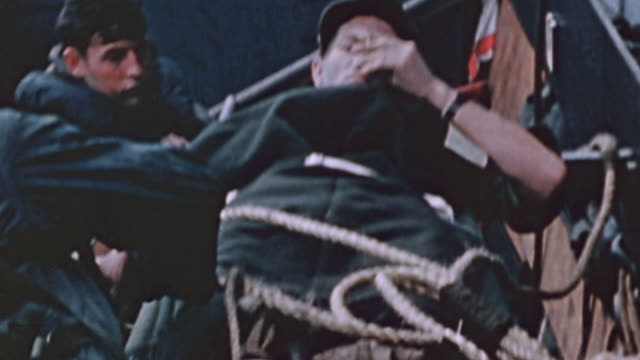 wounded soldier on stretcher being hoisted from higgins boat to uss lubbock during world war ii pacific campaign - schlacht um iwojima stock-videos und b-roll-filmmaterial