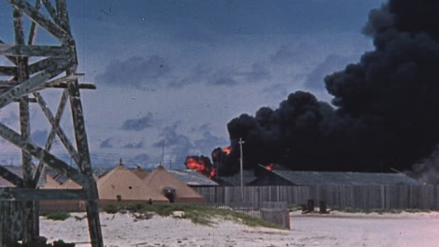 TS Fire in distance with massive column of thick black smoke billowing over barracks buildings during attack on Pearl Harbor / Hawaii United States
