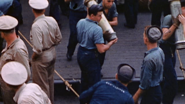 sailors aboard uss tennessee transferring naval shells and powder cases down gangplank to uss phelps / saipan mariana islands - mariana islands stock videos and b-roll footage