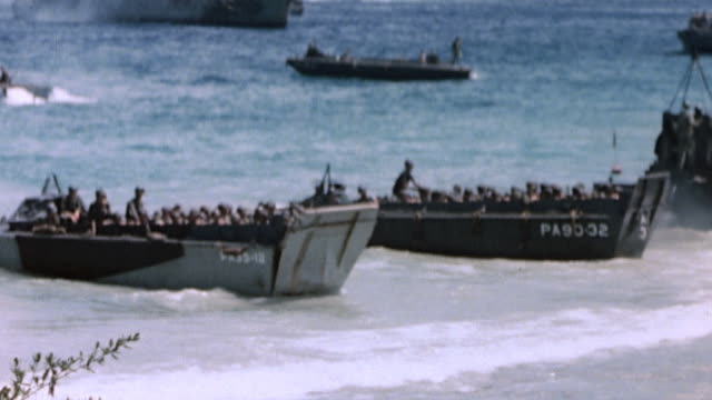 higgins boats loaded with marines arriving at beach on pacific island with us navy armada beyond - landungsboot stock-videos und b-roll-filmmaterial