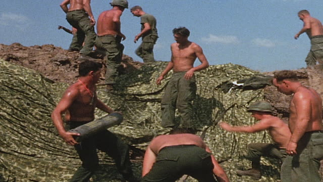 Shirtless soldiers forming human chain to move 155mm howitzer shells uphill / Vietnam