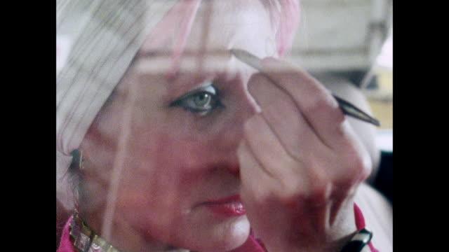 stockvideo's en b-roll-footage met zandra rhodes meets with friend / uk / zandra rhodes puts on makeup behind window with reflection / woman talks / zandra rhodes talks with friend in... - passagiersstoel