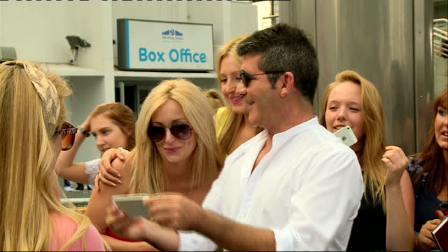 100th anniversary of elstree studios; r01081404 london: wembley arena: tv producer and presenter simon cowell posing for photograph with fans - wembley arena stock videos & royalty-free footage