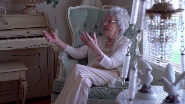 vídeos de stock e filmes b-roll de 100-year old woman having a cheerful conversation in her home - centenário