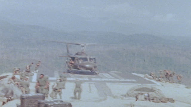 ha 101th airborne division soldiers evacuating from arriving uh1b at fire support base landing zone atop mountain / vietnam - 降り立つ点の映像素材/bロール