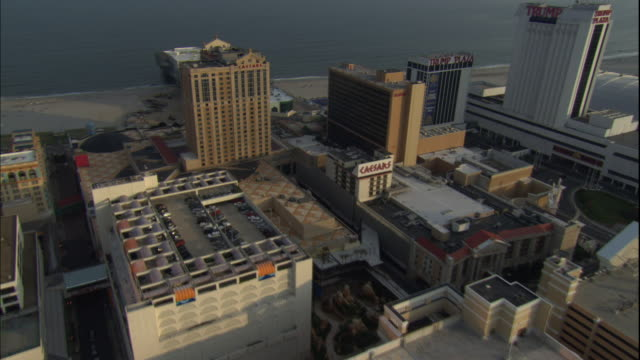 vídeos de stock, filmes e b-roll de 1080i hd aerial td ws moving over caesars complex tu ws moving around and away from caesars highrise resort hotel with trump plaza next door angled... - atlantic city