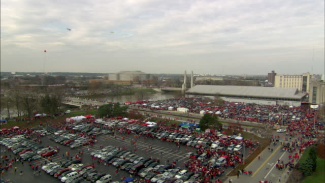 1080i HD XHA PAN OSU Parking lots w/ many people dressed in red walking others standing in Jesse Owens Memorial Plaza around Celebration For A...