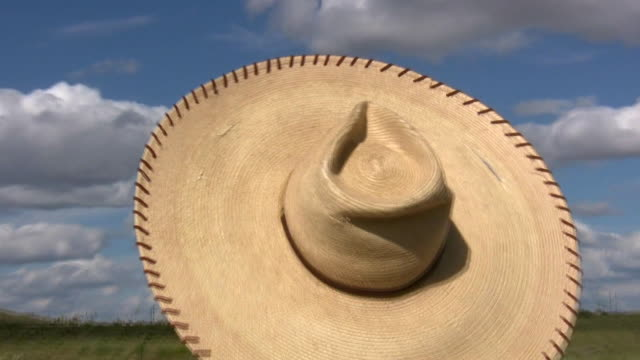 hd 1080i straw sombrero hat in wind 2 - straw hat stock videos and b-roll footage