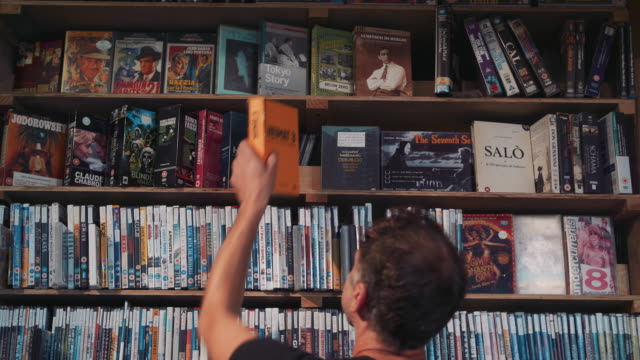 1080p stock footage of a man browsing through films in one of the few remaining dvd & vhs rental stores in the uk - video stock videos & royalty-free footage
