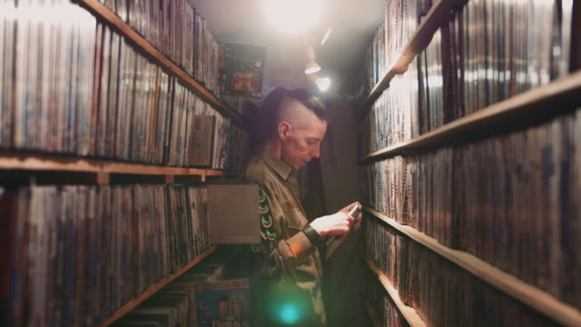 1080p stock footage of a man browsing through films in one of the few remaining dvd & vhs rental stores in the uk - dvd stock videos & royalty-free footage