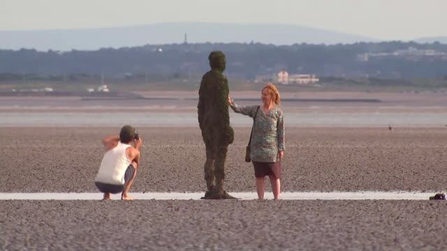 10th anniversary of anthony gormley statues 'another place' on crosby beach; england: merseyside: crosby: ext wide shot crosby beach cast iron figure... - mersey ferry stock videos & royalty-free footage