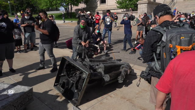 vídeos de stock e filmes b-roll de protesters pulled down the columbus statue with ropes on minnesota state capitol grounds protestors kick and spit on the statue - estátua