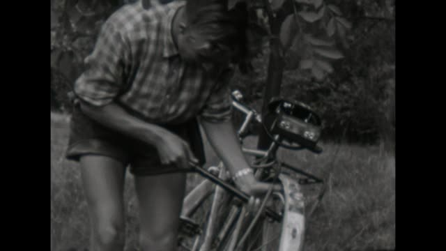 10th school class makes a trip with their bicycles in east - thüringen, young boy inflate air in the tires / shot in 1957 - weimar video stock e b–roll