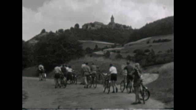 vídeos y material grabado en eventos de stock de 10th school class makes a trip with their bicycles in thüringen / visiting osterburg weida / shot in 1957 - bicicleta vintage