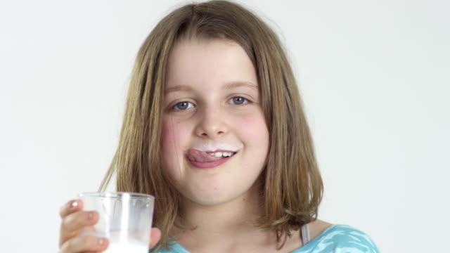 10-year-old girl drinks milk - close up - スタジオ撮影点の映像素材/bロール