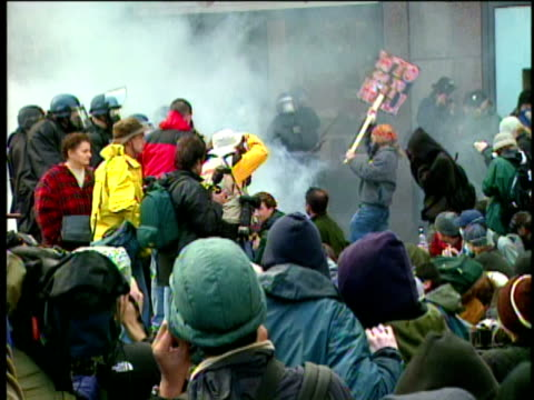 vídeos de stock e filmes b-roll de 12jan1999 ws police clash with protesters during wto conference in seattle police use tear gas / seattle washington usa - 1999