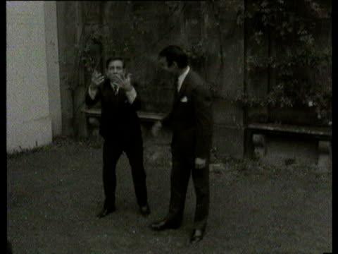vídeos y material grabado en eventos de stock de jul-1966 b/w two men in suits pretending to fight for soccer ball / united kingdom - traje completo