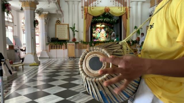 12th 2020: devotees singing devotional song, playing musical instrument during hindu faith celebrate krishna janmastami at iskon temple in guwahati,... - 信者点の映像素材/bロール