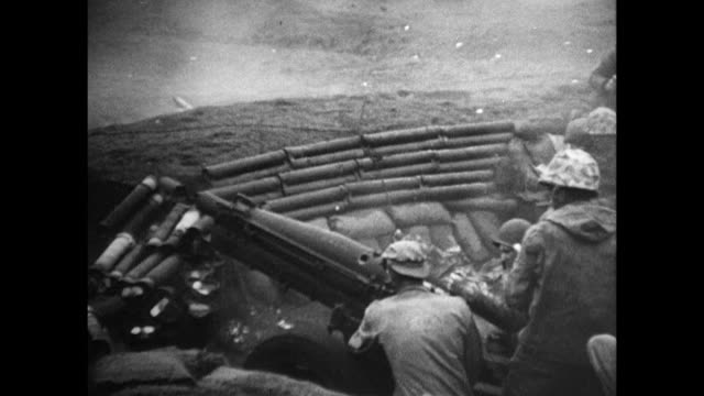vs 12th marine artillery regiment on beach w/ cannons firing on mount suribachi aka hot rocks various explosions smoke firing reloading shells - battle of iwo jima stock videos & royalty-free footage
