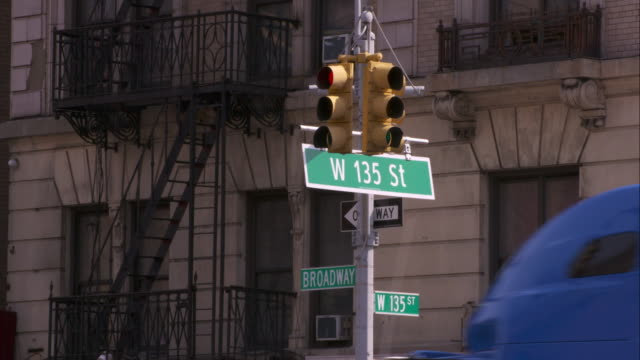 135th and broadway street sign in harlem.  cars drive in and out and obscure the street sign. - harlem stock videos & royalty-free footage