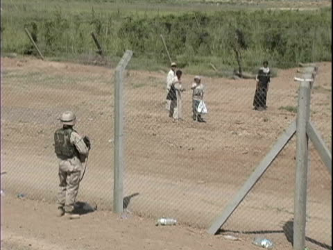 15th jan 2004 montage local children playing outside perimeter fence / lsa anaconda iraq / audio - 2004 stock videos & royalty-free footage