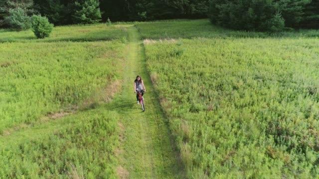 stockvideo's en b-roll-footage met 15-jaar oude tiener meisje fietsen op het spoor in de weilanden bij de ed. poconos (pennsylvania) - 14 15 years