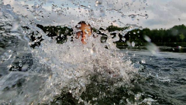 stockvideo's en b-roll-footage met 15-jaar oude tiener meisje zwemmen en spetteren in het meer. - 14 15 years