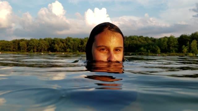15-jaar oude tiener meisje zwemmen en spetteren in het meer.