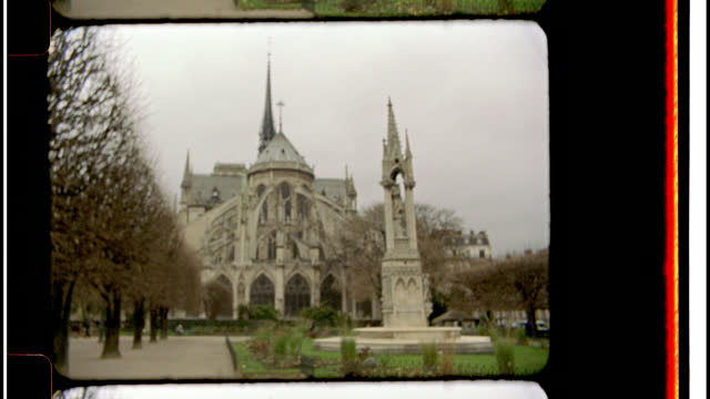 16mm bolex film footage. view of the notre dame cathedral flying buttresses from the back courtyard. - cobblestone stock videos and b-roll footage