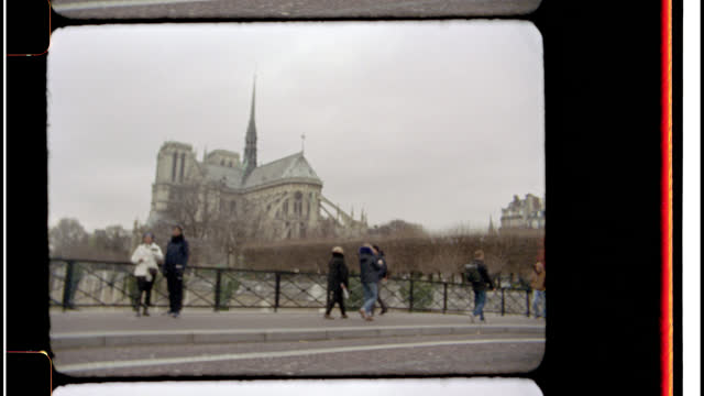 stockvideo's en b-roll-footage met 16mm. bolex film footage. view of the notre dame cathedral in paris, france as tourists and locals cross a cobblestone bridge over st. joseph river. - kassei