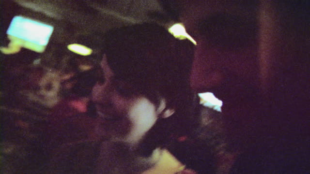 16mm film footage of young couple shopping for vinyl albums in record store