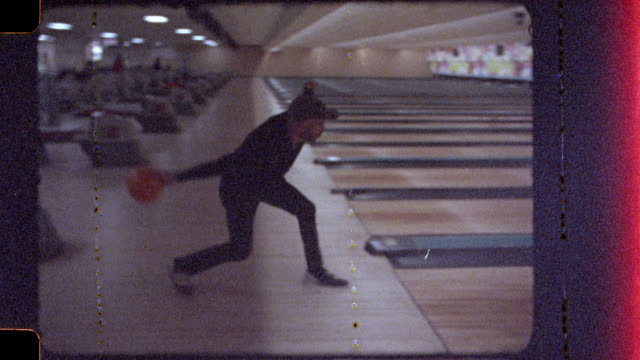 16mm film footage of young man walking through bowling alley and bowling with friends. - freizeitspiel stock-videos und b-roll-filmmaterial