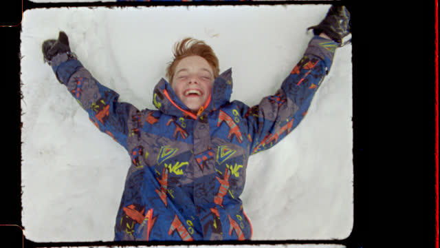 16mm. happy young boy does snow angels sticking out his tongue and smiling - ski holiday stock videos & royalty-free footage