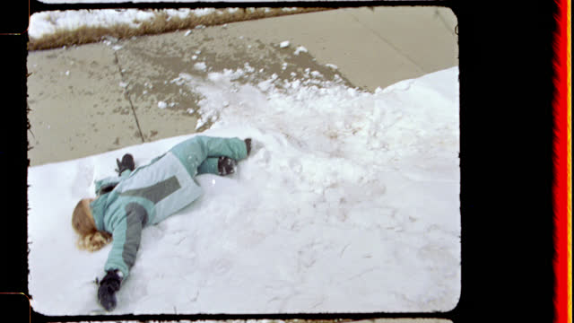16mm. happy young girl rolls and her older brother sleds down snowy hill in front of steamboat springs lodge - public celebratory event stock videos & royalty-free footage