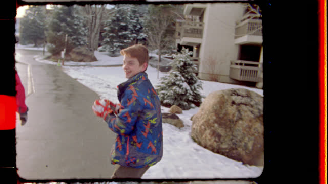 vídeos de stock, filmes e b-roll de 16mm. playful young boy throws a snowball at his unsuspecting younger sister - filmando