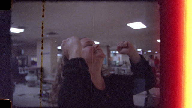 16mm. Woman bowls a strike and celebrates with friends in bowling alley.