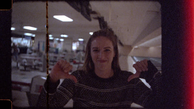 16mm. young woman bowling with friends rolls gutter ball and gives thumbs down to camera. - verlust stock-videos und b-roll-filmmaterial