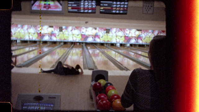 16mm. young woman strikes a pose as she bowls a strike and celebrates with friends in bowling alley. - ボウリング点の映像素材/bロール