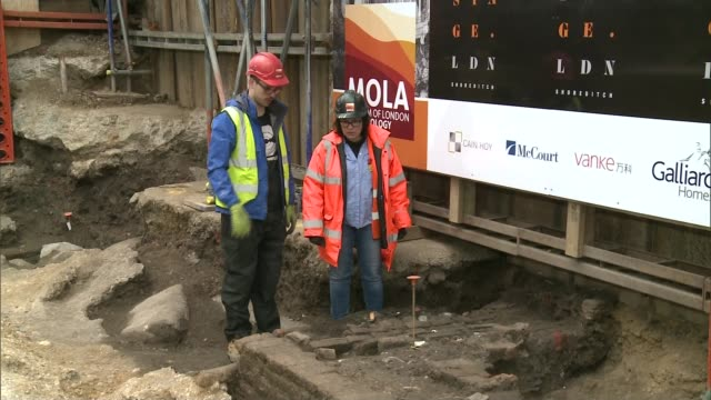 16th century shakespearian playhouse in shoreditch excavated lib tx london shoreditch ext two archaeologists in hivis gear chatting on building site... - playhouse stock videos & royalty-free footage