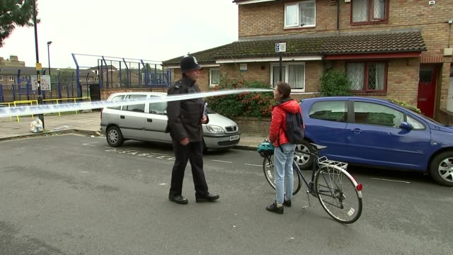 16yearold boy becomes 10th teenager to be stabbed to death in london in 2015 england london kennington newington estate ext police officer chatting... - ロープ仕切り点の映像素材/bロール